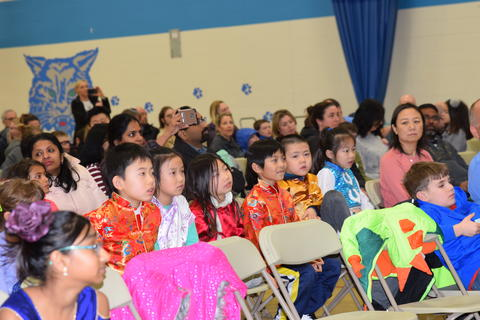 Audience with 6 seated young students watching performance