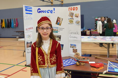 Smiling girl in Greek costume with Greece project board