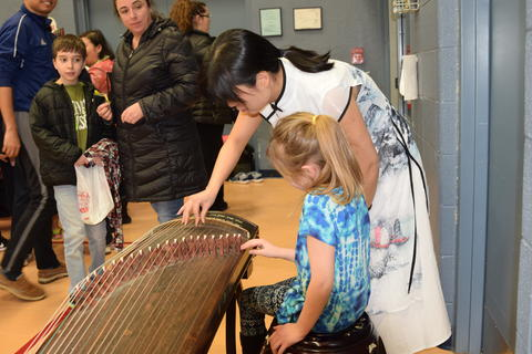 Woman demonstrating playing stringed instrument for young girl