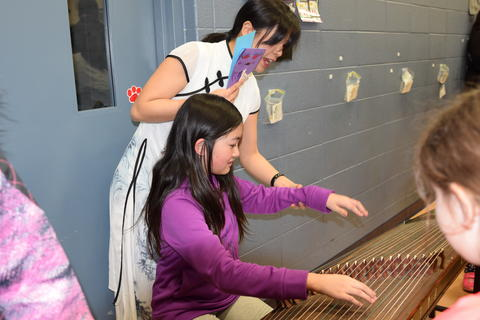 woman placing young girl's hands on stringed instrument