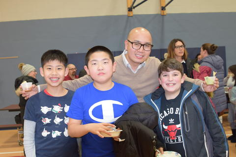 male teacher and three young boys smiling