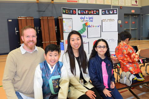 male and female teacher and young students smiling with World Cultures Club project board