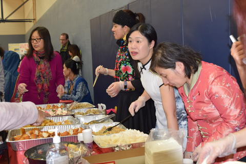 women in cultural dress serving food