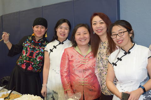 five women in cultural dress smiling