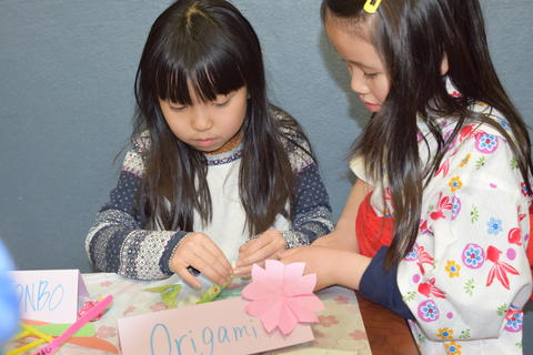 two young girls creating origami