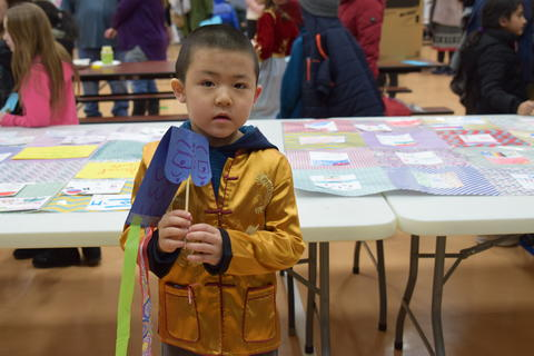 young boy with paper dragon craft