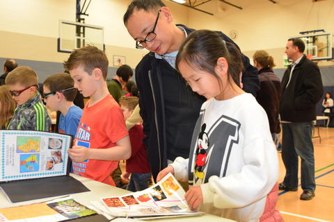 father and children looking at display books