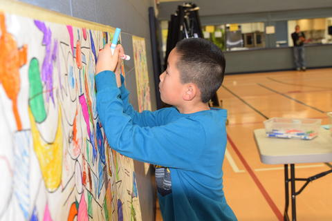 boy coloring mural with markers
