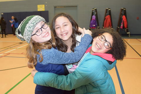 three young girls smiling and hugging
