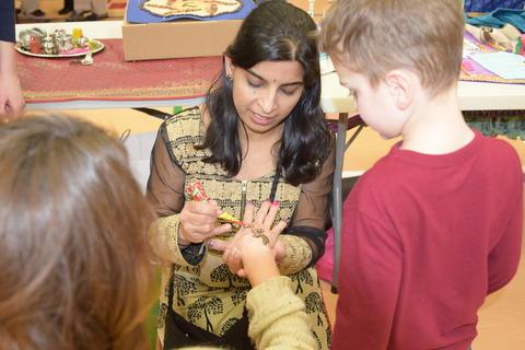 woman painting henna design on girl's hand