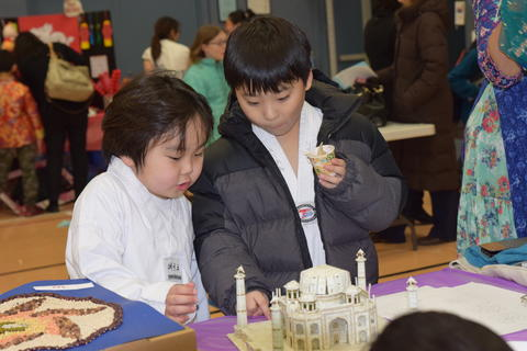 young brothers examining cardboard building on tabletop