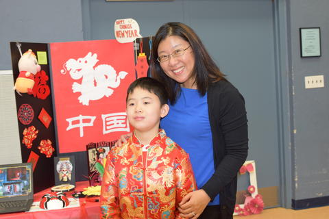 smiling mother and son with Chinese project display board
