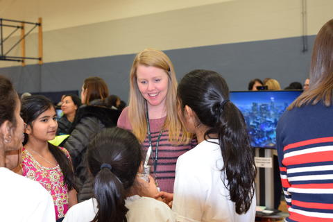 smiling female teacher talking with young girls