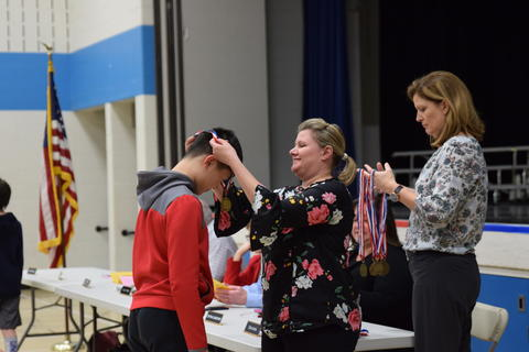 young boy receiving medal from Board of Education member