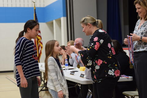 small girl receiving medal from Board of Education member