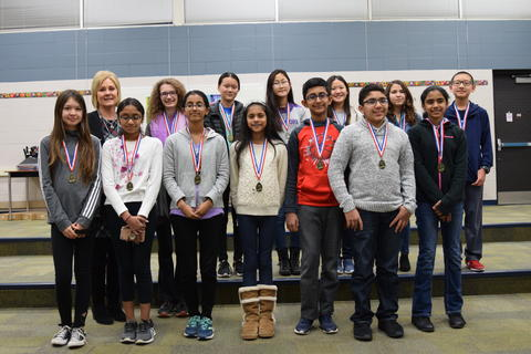 smiling students posing wearing medals