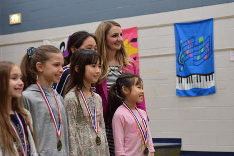 students with medals posing for photo