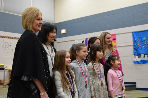 smiling students with medals and teachers