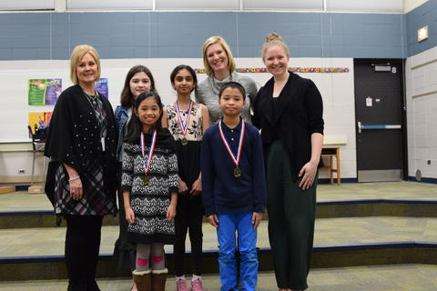 smiling students with medals posing with teachers