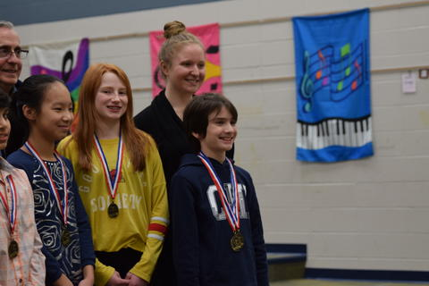 3 smiling students wearing medals posing with teacher