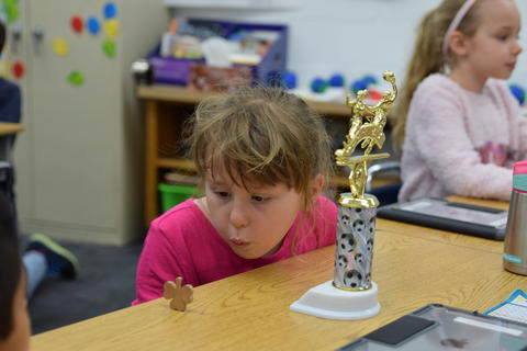 young girl with trophy blowing to move a toy over desktop