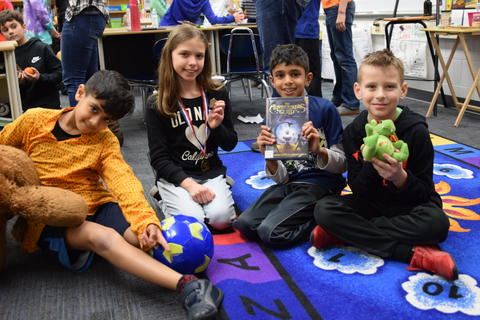 four young students seated on floor posing with toy, book, ball