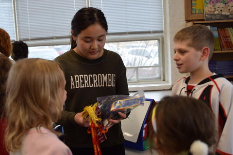 young student group looking at items held by girl in group