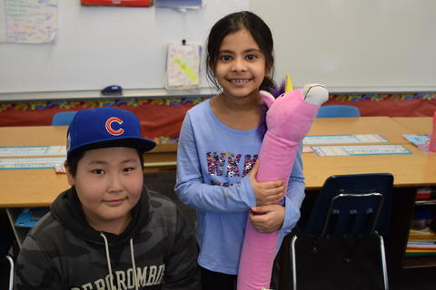 boy wearing Cubs baseball cap and girl with stuffed toy