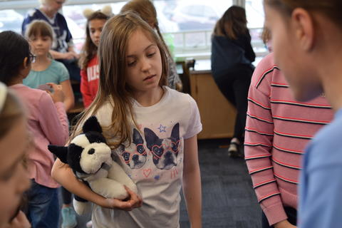 young girl holding toy dog and watching classmates