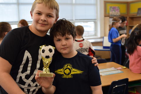 two young boys posing with soccer trophy