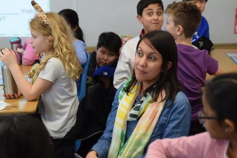 smiling teacher listening to student