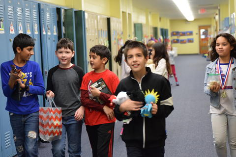 elementary students in school hallway carrying toys and book