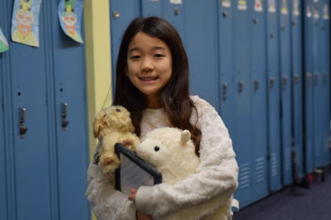 young girl holding two small toy animals