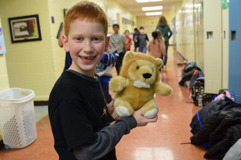 young smiling boy holding small toy animal