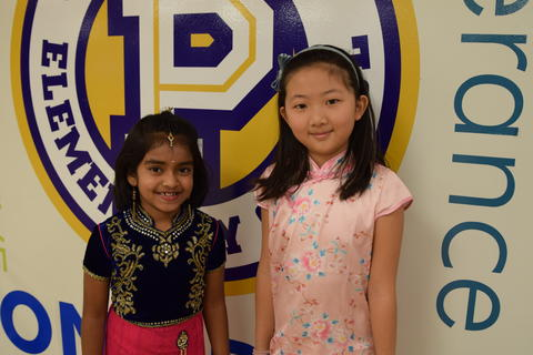 two smiling young girls in cultural dress by school logo