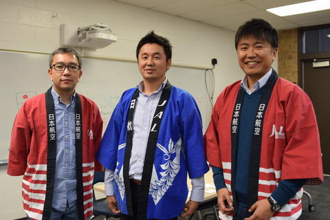 three smiling men wearing cultural clothing