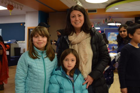 smiling mother and two young daughters wearing winter coats