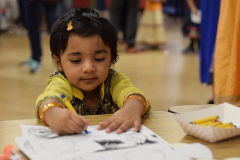 very young girl in cultural dress coloring with crayon