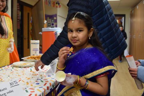 Smiling young girl in cultural dress, sampling food