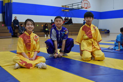 two young boys and girl wearing martial arts clothing and seated on mat