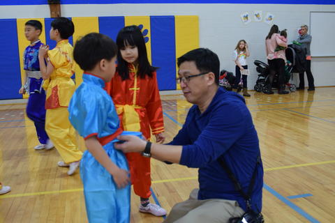 man tying belt on young boy's martial arts clothing