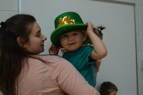 young boy wearing green hat with shamrock design, held by mother