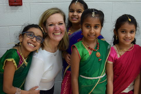 smiling woman surrounded by four smiling young girls wearing cultural clothing