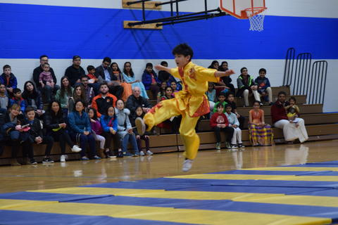 young boy doing leaping kick in martial arts performance