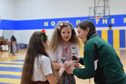 young female teacher handing microphone to two girls wearing cultural dress