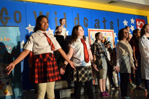 young girls onstage singing and gesturing
