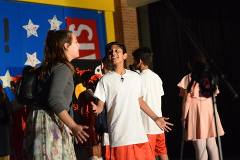 young boy and girl onstage singing to each other