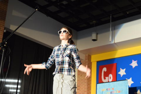 young girl wearing sunglasses onstage talking