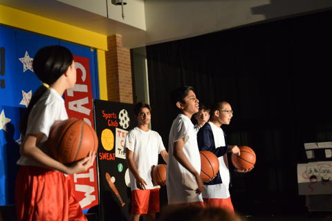 young boys onstage holding basketballs
