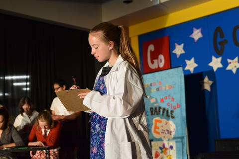 young girl wearing lab coat onstage performing